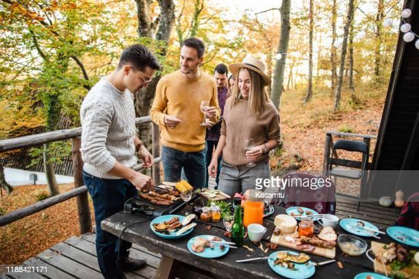 gemeinsam essen im freien zubereiten - grill zubereitung stock-fotos und bilder