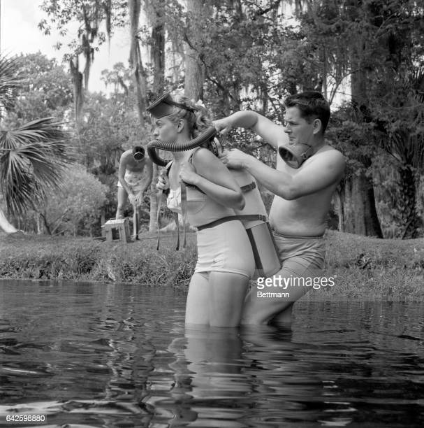 """Preparing for a """"lab"""" session, teacher Bruce Mozert, helps Ginger into an aqualung so she can breathe underwater. On the bank, Bill Ray pumps air..."""