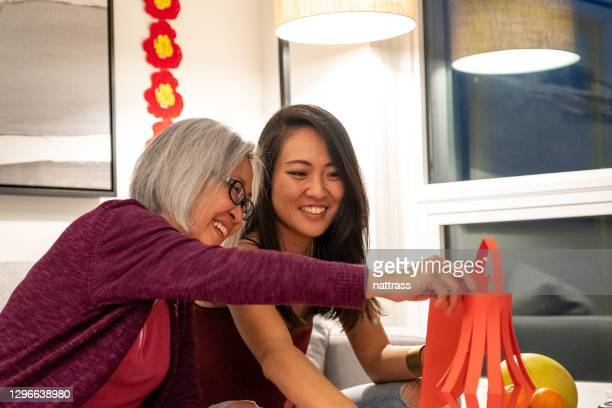 preparing for chinese new year celebrations - 60 69 years stock pictures, royalty-free photos & images