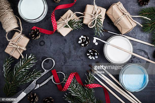 Preparing for Christmas, decoration of natural gifts with copy space. Top view of brush for drawing,  ribbon, scissors, paint, gift boxes in kraft packaging, twigs Christmas trees