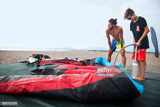 preparing for kite surfing - air pump stock photos and pictures