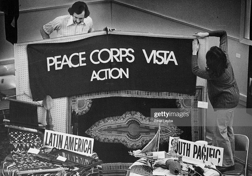JAN 6 1975, JAN 7 1975; Preparing For The Fair; Jim Weidman and Jo Ellen McNeal put up a Peace Corps banner, right, at International House, 1600 Logan St., for the Peace Corps/Vista fair; to be held there Saturday from noon to 5 p.m. Weidman then po-ísitioned a model canoe, below, from the island of Woleai for the fair. Weidman served as a Peace, Corps volunteer in Thailand. Miss Mc-íNeal served in Barbados.;