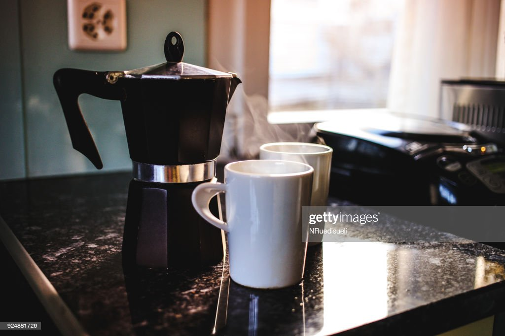 Preparing fresh coffee in moka pot on electric stove. Pouring hot steaming coffee into two white mugs. : Stock Photo