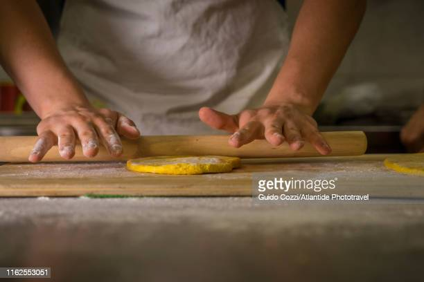 preparing fresh egg pasta dough with a rolling pin - image stock pictures, royalty-free photos & images