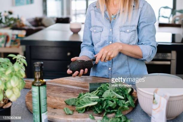 preparing healthy food at home in kitchen - young women stock pictures, royalty-free photos & images