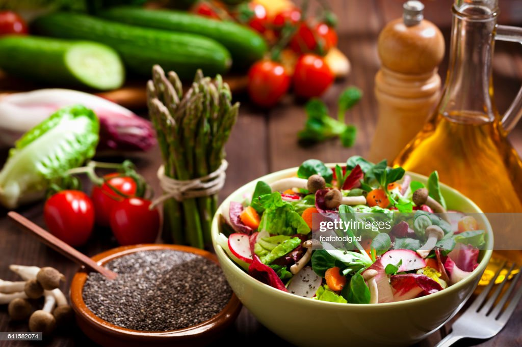 Preparing healthy salad with chia seeds on rustic wood table : Stock Photo