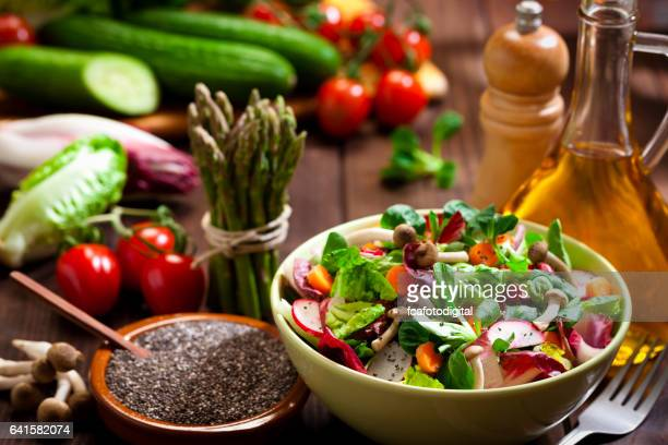 Preparing healthy salad with chia seeds on rustic wood table