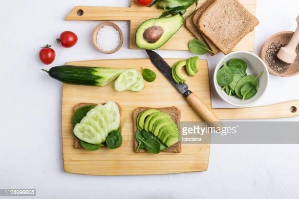 preparing healthy vegan sandwiches  with green vegetables - skärbräda bildbanksfoton och bilder