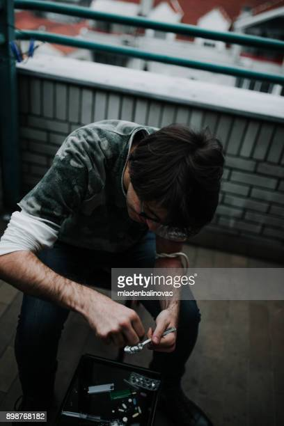 preparing his dose - heroin addict arm stock photos and pictures