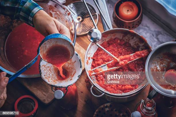 preparing homemade tomato sauce and preserving in bottles - tomato sauce stock pictures, royalty-free photos & images