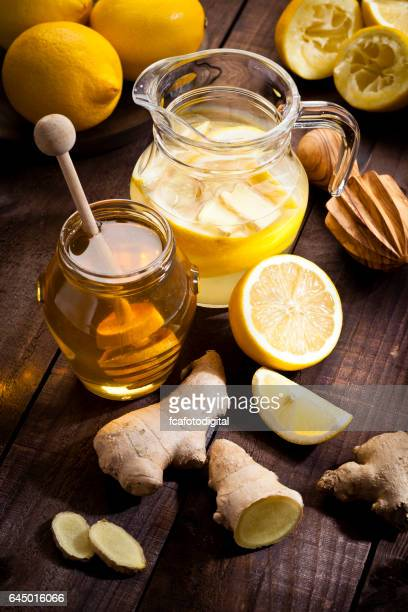 Preparing lemon infused water with honey and ginger