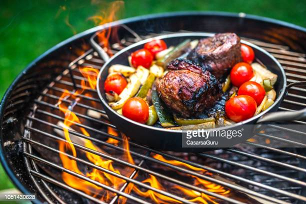 preparing meat with vegetables in frying pan on barbecue grill - grill concept stock photos and pictures