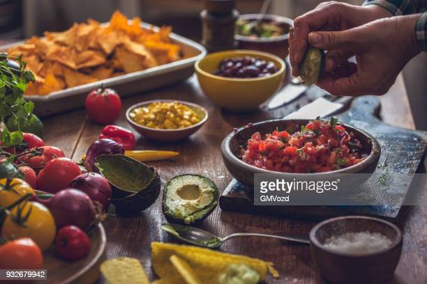 preparing mexican tacos with spicy salsa and guacamole - salsa sauce stock photos and pictures
