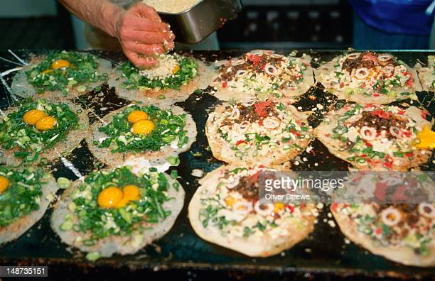 preparing okonomiyaki, or japanese pizza. - okonomiyaki stock pictures, royalty-free photos & images