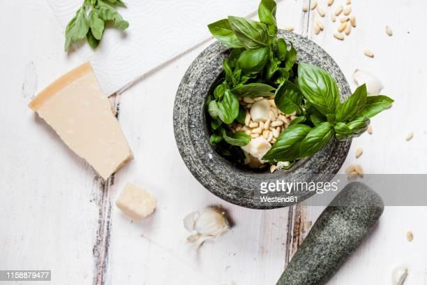 preparing pesto alla genovese with mortar - pesto stock pictures, royalty-free photos & images