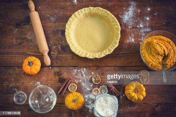 preparing pumpkin pie for the holidays at home - pastry dough stock pictures, royalty-free photos & images