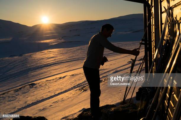 Preparing skis at Sunset on Hardangervidda plane in Norway on the end of April