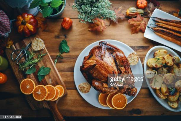 preparing stuffed turkey for holidays in domestic kitchen - thanksgiving holiday stock pictures, royalty-free photos & images