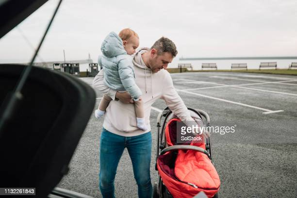 preparing the pushchair in the parking lot - carriage stock pictures, royalty-free photos & images