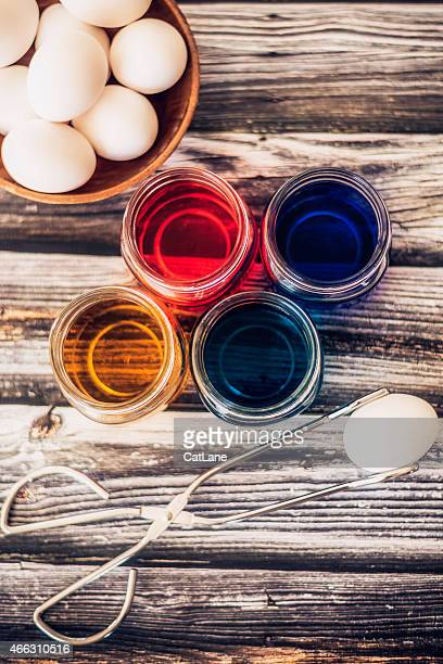 Preparing to dye eggs for Easter. Picking-up egg for dyeing.