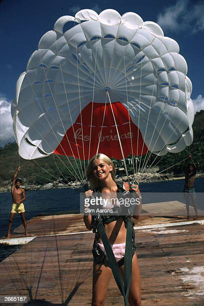 Preparing to go paragliding in Acapulco a young blonde woman holds on firmly to her parachute harness