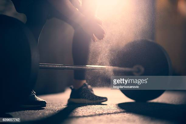 preparing to lift dumbell in a gym - crossfit stock pictures, royalty-free photos & images