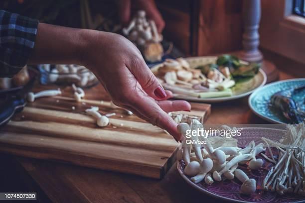 preparing tom yum thai soup with shrimps, enoki mushrooms and fresh chili - enoki mushroom stock pictures, royalty-free photos & images