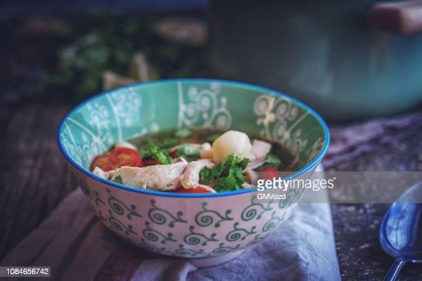 Preparing Tom Yum Thai Soup with Shrimps, Enoki Mushrooms and Fresh Chili