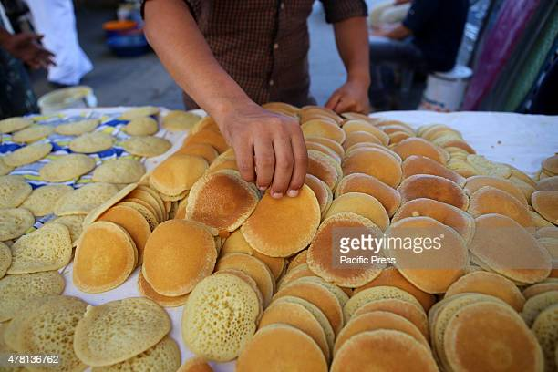 Preparing traditional pancakes known as ''Qatayef'' in a street market on the fifth day of the holy month of Ramadan in Rafah in the southern Gaza...