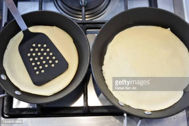 preparing two  pancakes in a frying pan - rafael ben ari imagens e fotografias de stock