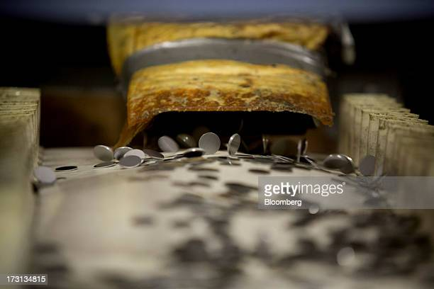 Prepressed coins fall on to a conveyor belt at the Royal Canadian Mint in Winnipeg Ontario Canada on Friday July 5 2013 The Canadian dollar rose from...