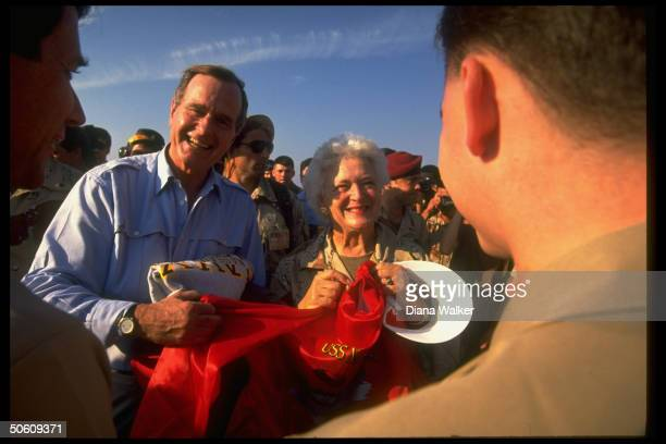 Pres Barbara Bush holding USS Nassau souvenirs on bd US warship spending gulf crisis Thanksgiving w sailors on duty in Persian Gulf off coast of...