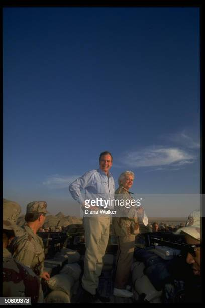 Pres Barbara Bush poised on back of army truck ringed by gulf crisisduty troops at 1st Marine Division desert command post spending Thanksgiving in...