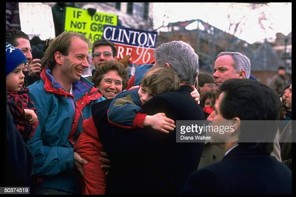 Pres Bill Clinton hugging youngsters greeting supporters in street jaunt getting jump start on his reelection campaign