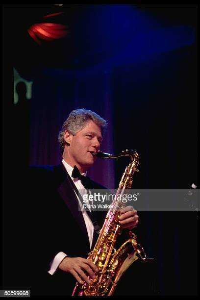 Pres Bill Clinton playing saxophone at DC Armory Ball during inaugural wk festivities