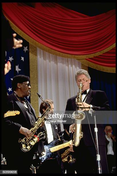 Pres. Bill Clinton playing saxophone, jamming w. Musician Clarence Clemons at DC Armory Ball during inaugural wk. Festivities.