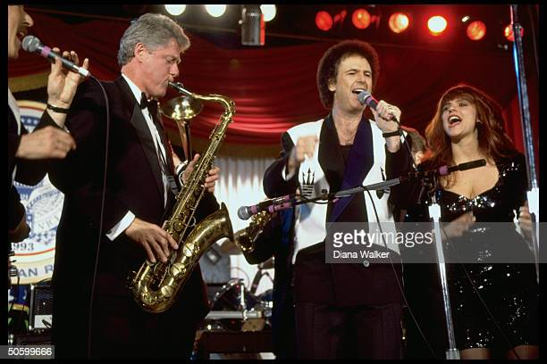 Pres. Bill Clinton playing saxophone, jamming w. Musicians onstage at DC Armory Ball during inaugural wk. Festivities.
