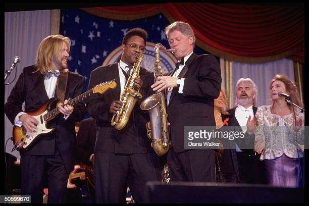 Pres. Bill Clinton playing saxophone, jamming w. Musicians onstage at DC Armory Ball during inaugural wk. Fete.