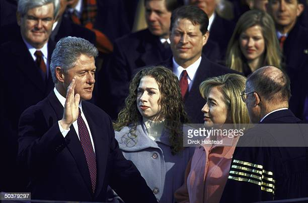 Pres Bill Clinton raising hand taking oath of office in his 2nd term Inaugural Day swearin wife Hillary Rodham Clinton daughter Chelsea VP Gore House...
