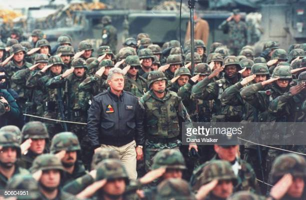 Pres Bill Clinton recieving salute reviewing US soldiers in visit to troops on peacekeeping mission enforcing USbrokered peace accord in civil...