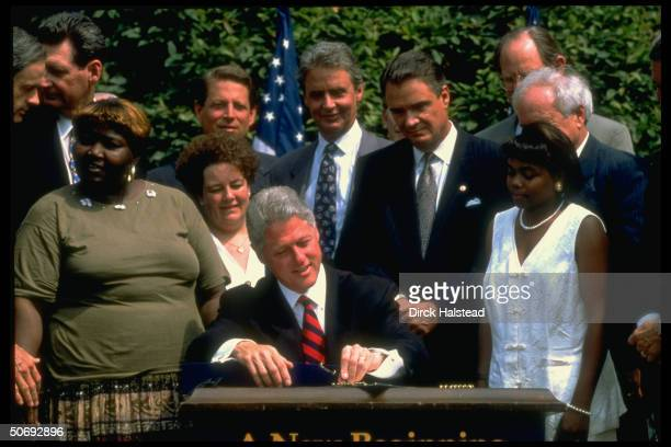 Pres Bill Clinton signing welfare reform bill in WH Rose Garden w former welfare recipient women others incl VP Gore Sen Breaux
