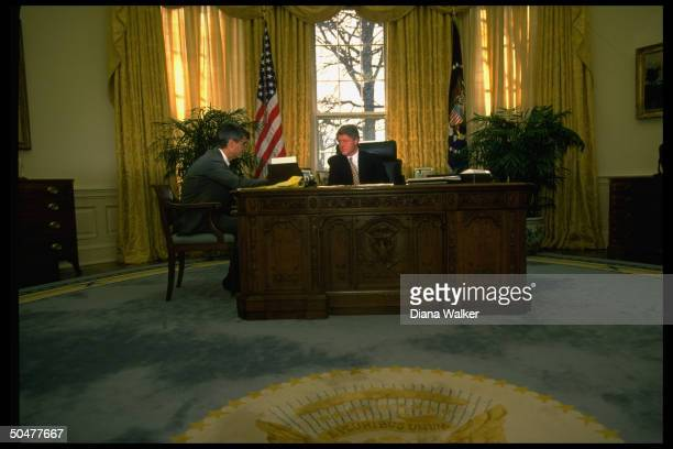 Pres Bill Clinton sitting at his desk in WH Oval Office mtg w NEC chmn Robert Rubin