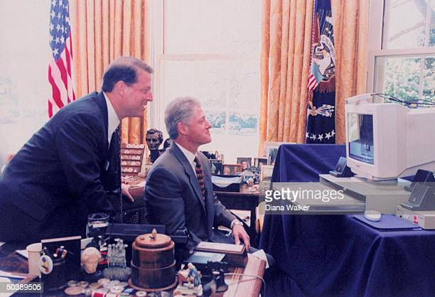 Pres Bill Clinton smiling at image on his computer screen VP Al Gore looking over his shoulder in White House Oval Office