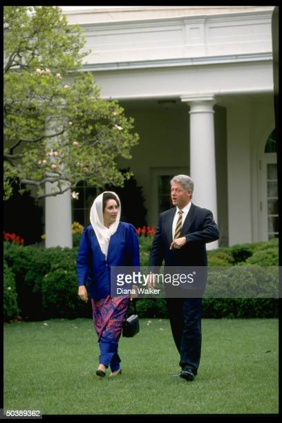 Pres. Bill Clinton & visiting Pakistani PM Benazir Bhutto out on stroll in White House Rose Garden.