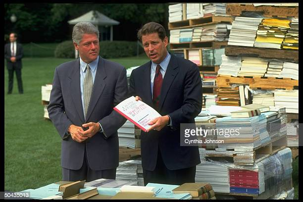 Pres Bill Clinton VP Al Gore presenting VP's Report of Natl Performance Review framed by piled govt regulations bks at WH