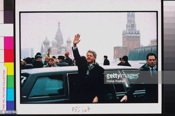 Pres. Bill Clinton waving, standing in front of his limo, secret serviceman at his side, in Red Square during summit.