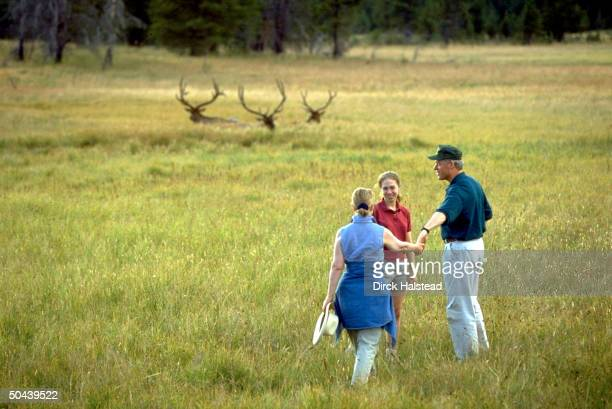 Pres Bill Hillary Rodham Clinton holding hands facing daughter Chelsea out for 1st family vacation stroll in field graced by trio of elk