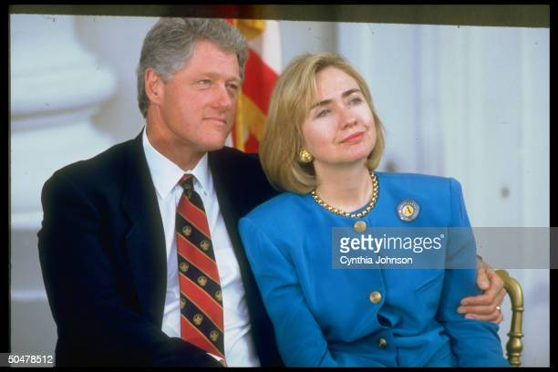 Pres Bill Hillary Rodham Clinton in intimate moment sitting close together he w affectionate arm around her during WH Americorps event