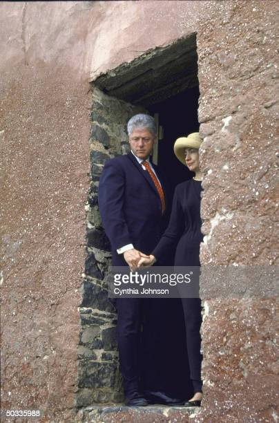 US Pres Bill Hillary Rodham Clinton standing in Door of No Return slave quarters portal leading to ocean where slaves were put on ships for transport...