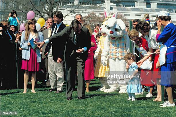 Pres Bush bending playing egg w grandkid Ellie w WH Easter invitees incl actor Christopher Reeve easter bunnies
